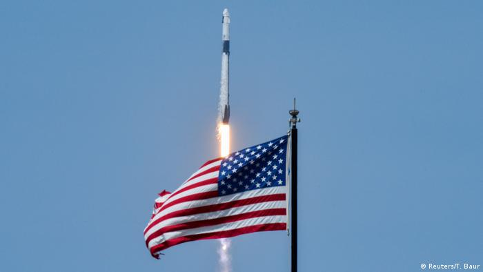 SpaceX's Falcon 9 rocket launches in Florida behind a USA flag