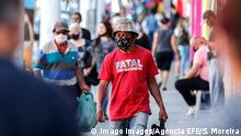 People with face masks walk in front a closed stores due the coronavirus restrictions in Sao Paulo (Imago Images/Agencia EFE/S. Moreira)