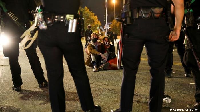 Police in LA surround two people sitting on the ground (Reuters/P.T. Fallon)