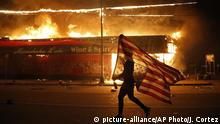 A protester carries a U.S. flag upside down, a sign of distress, next to a burning building Thursday, May 28, 2020, in Minneapolis. Protests over the death of George Floyd, a black man who died in police custody Monday, broke out in Minneapolis for a third straight night. (AP Photo/Julio Cortez) |