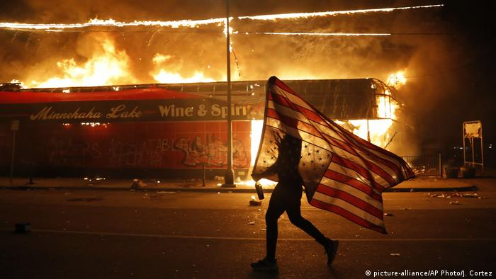 A protester carries a U.S. flag upside down, a sign of distress, next to a burning building