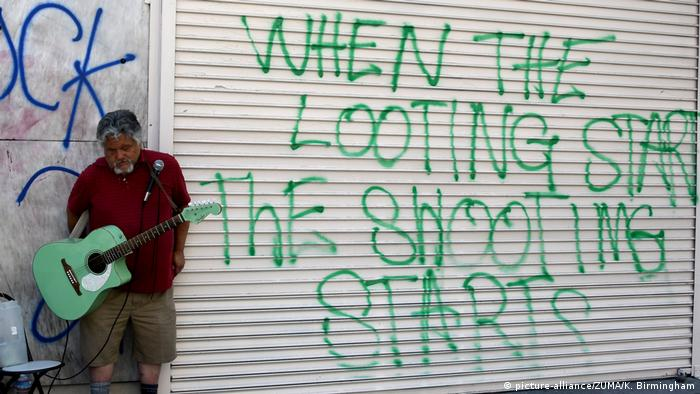 A man plays guitar next to a graffiti sign with When the Looting Starts the Shooting Starts