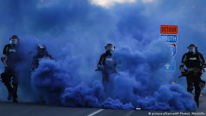 Policiais avançam em meio a nuvem de gás azul
