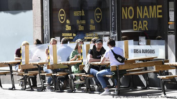 People sit outside a restaurant in Stockholm