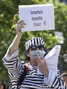 A woman wearing a prisoner costume holds a sign in German reading: Vaccinations will set you free (picture-alliance/dpa/B. Roessler)