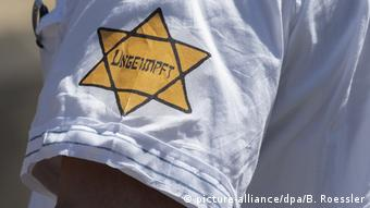 A yellow 'Jewish star' on a sleeve, with the word 'ungeimpft' (unvaccinated)