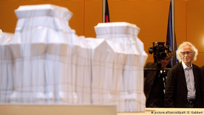 Christo stands behind a model of the wrapped Reichstag (picture-alliance/dpa/K.-D. Gabbert)