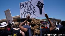 Участница акции протеста с плакатом Black Lives Matter (Жизни чернокожих имеют значение)