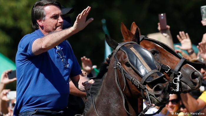 Bolsonaro waves to supporters on horseback in Brasilia