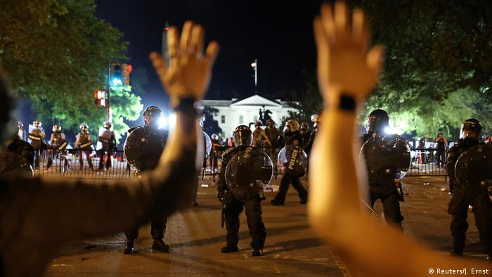 Protesters hold their hands up in front of law enforcement personnel as demonstrators rally at the White House