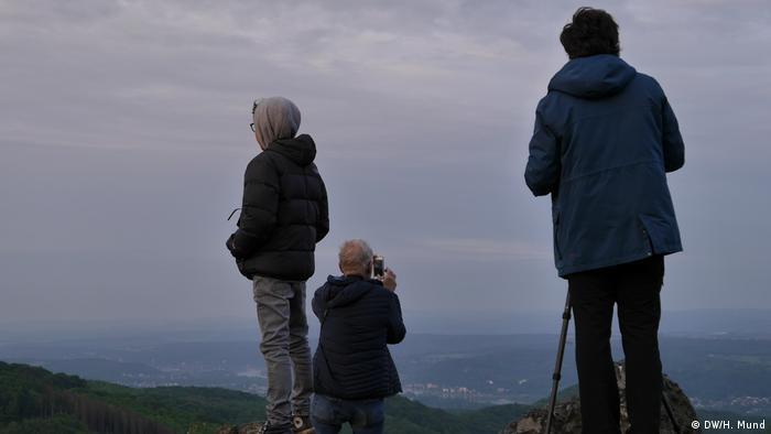 Drei Mann warten in der Morgendämmerung auf dem Ölberg, Siebengebirge (Rheinland)