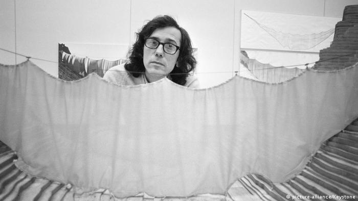 Christo posiert hinter einem Vorhang