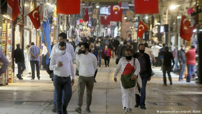 People wearing masks stroll through a bright, grand marketplace with many red Turkish flags.
