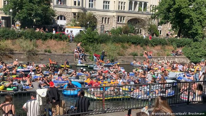 Dozens of people crowd together on rubber dinghies on a Berlin canal