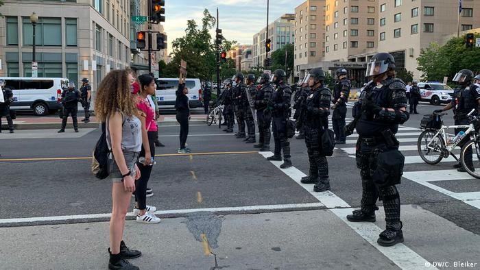 Protesters in shorts and t-shirts stand across from police in helmets and full riot gear (DW/C. Bleiker)
