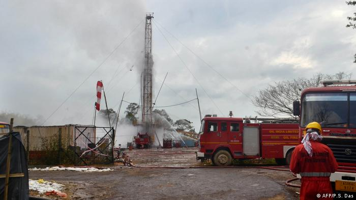 An Oil India firefighter oversees work near the oil well site after the blast