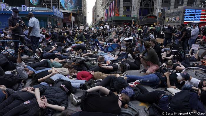 Демонстранты с руками, заведенными за спину, лежат на Тайм-Сквер