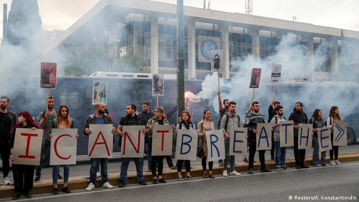 Участники демонстрации в Афинах держат плакаты с буквами, образовывающими предложение Я не могу дышать