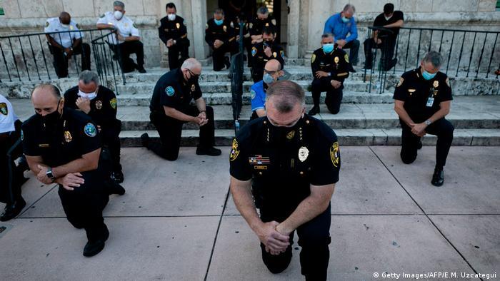 Полицейские стоят на одном колене перед протестующими