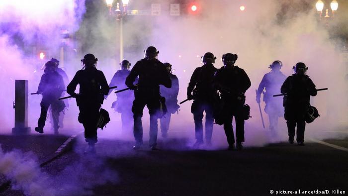 Policías traspasan nubes de gases lacrimógenos que otra unidad había lanzado a los manifestantes contra la discriminación racial.