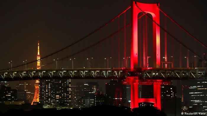The Rainbow Bridge is lit up in red, to signalise that the coronavirus disease