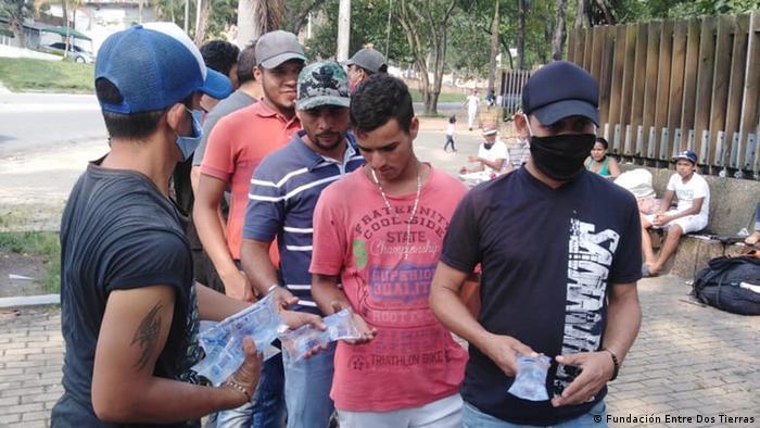 Refugiados venezolanos reciben agua en el camino hacia la frontera, de regreso a su país.