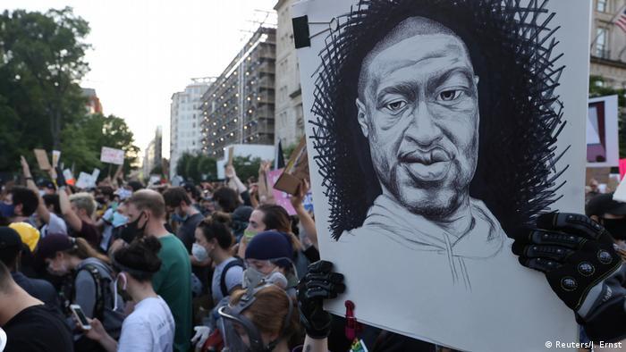 Учасник акції протесту у Вашингтоні тримає плакат із зображенням Джорджа Флойда