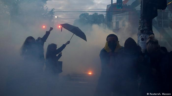Protester holding up umbrella amid smoke in Seattle George Floyd