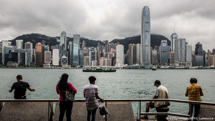 People sit on the waterfront of Victoria Harbor in Hong Kong