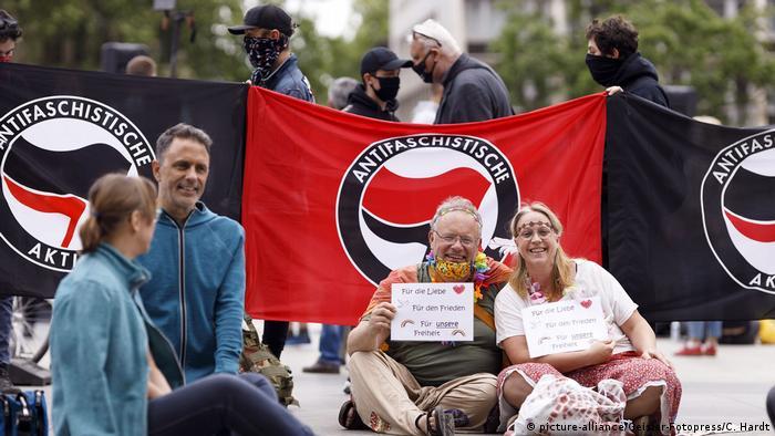 Cologne, 16 mai 2020: Deux personnes sont assises avec des pancartes appelant à l'amour et à la paix dans le monde devant l'action antifasciste du mouvement antifasciste.  Derrière eux, de jeunes manifestants brandissent des drapeaux avec des masques noirs.  La contre-manifestation a été appelée en réponse à une autre manifestation contre les restrictions aux coronavirus en Allemagne.