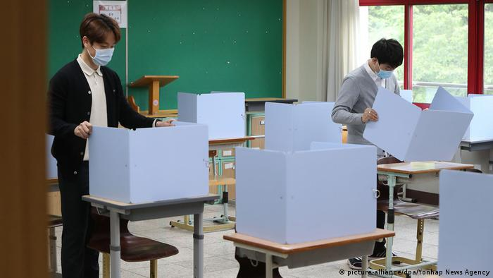 Teachers check partition walls installed to ensure students' safety as they return to classrooms in Daegu, South Korea. In late February, the city of Daegu reported the first large coronavirus outbreak outside of China, resulting in a huge spike in South Korea's COVID-19 infections.