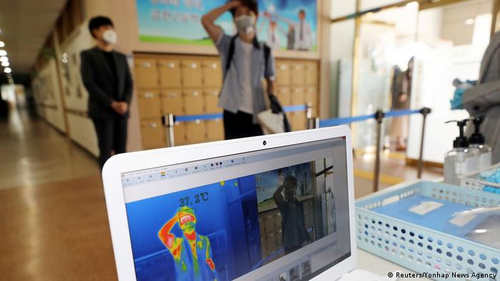 Students wait in line as staff conduct temperature checks with a thermal imaging camera in Chungju, South Korea. The latest phase of reopening has brought nearly 1.8 million children back to school.