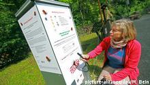 ARCHIV - Wanderin Christine Prem-Vogt aus Berlin informiert sich am 26.06.2014 über einen Zeckenschutz-Automaten. Für einen Euro können sich die Wanderer mit dem Zeckenschutzmittel benetzen. Foto: Matthias Bein/dpa (zu dpa-Korr. lah «Automaten gegen Zecken - Premiere im Harz» vom 27.07.2014) +++(c) dpa - Bildfunk+++ | Verwendung weltweit
