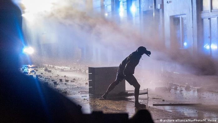 Protester hurling stones at water cannon (picture-alliance/NurPhoto/M. Heine)