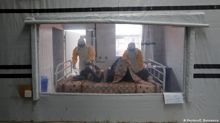 An Ebola patient lies in bed as two health workers examine him.