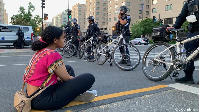 A young woman sits on the street in front of a row of police (DW/C. Bleiker.)