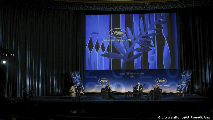 A discussion panel at the Cannes Festival sits on a dramatically lit stage. Behind the panel members is the logo of the Cannes Film Festival 2020.