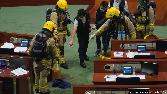 Firefighter and police inspect the main chamber of the Legislative Council after a pro-democracy lawmaker dropping a pot of a pungent liquid in Hong Kong