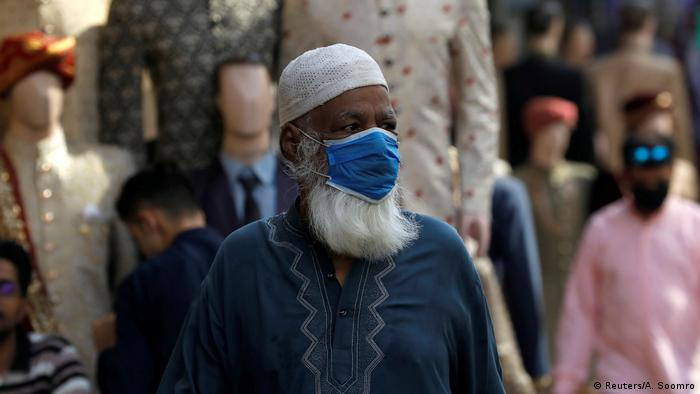 A man wearing a protective face mask, walks past shops at a market, as the outbreak of the coronavirus disease