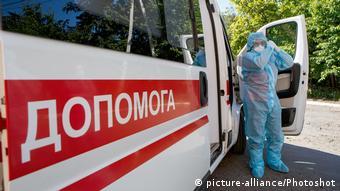 Украинская машина скорой помощи и врач в защитном костюме