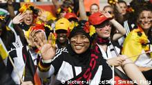 A girl in a headscarf cheers on Germany's handball team