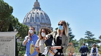 Туристы в масках на фоне купола собора Св. Петра в Ватикане