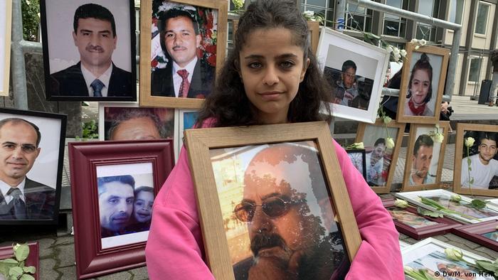 أمام محكمة كوبلنز ـ الناشطة السورية وفاء مصطفى وهي تحمل صورة والدها المختفي وسط صور بعض ضحايا نظام الأسد
