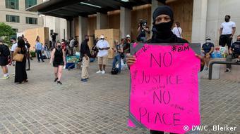 25-летний Брайан на демонстрации в Вашингтоне с плакатом Без справедливости нет мира