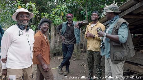 Dreharbeiten von DA 5 BLOODS mit Regisseur und vier Darstellern bei einer Drehpause vor Kulissen (aka DA FIVE BLOODS) (picture-alliance/Everett Collection/Netflix/D. Lee)