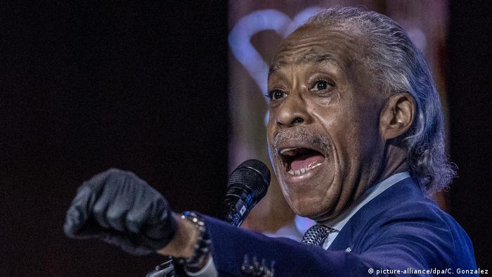 Al Sharpton speaking into a microphone with his left arm raised to shoulder height