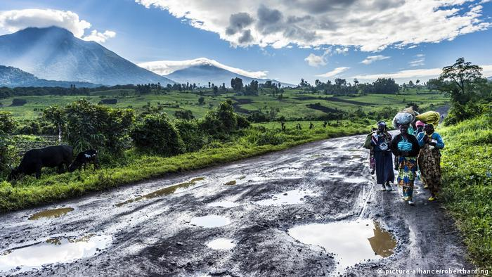 Women walk along a muddy road in Virunga National Park