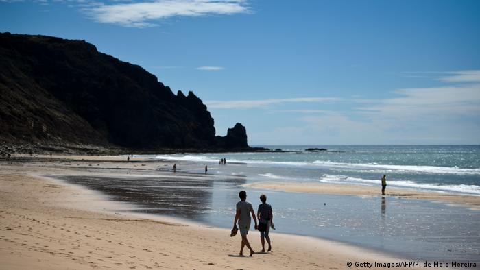 People walking along the beach of Praia da Luz, Algarve, Portugal