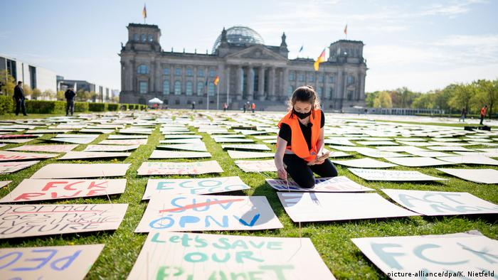 A protester sits among the posters laid out in front of the Reichstag buiding