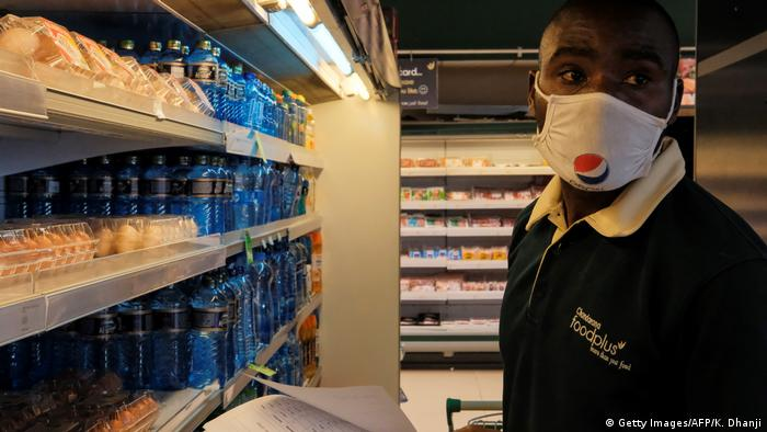 An employee at a supermarket in Kenya stocks shelves while wearing a face mask